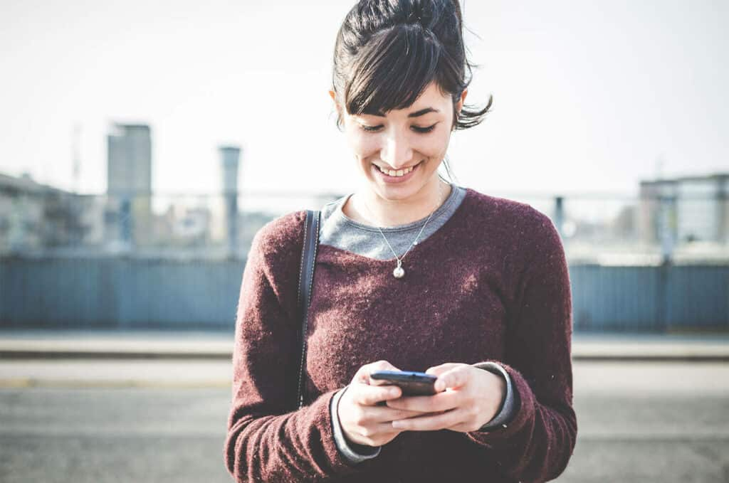 young, hip woman, smiling while looking at her cell phone