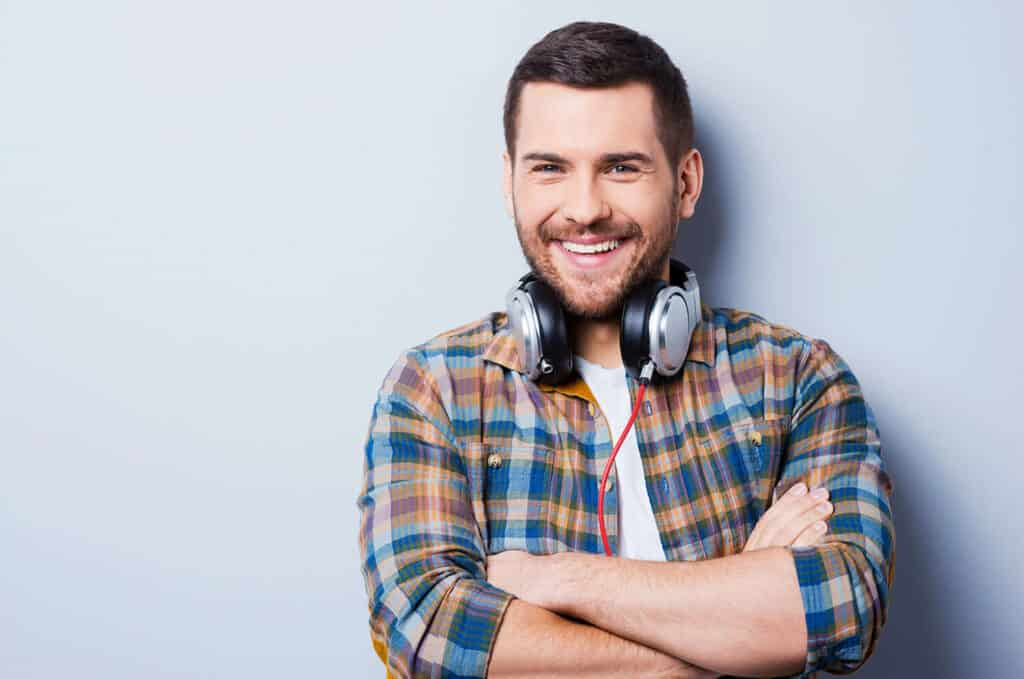 smiling man wearing headphones and plaid shirt