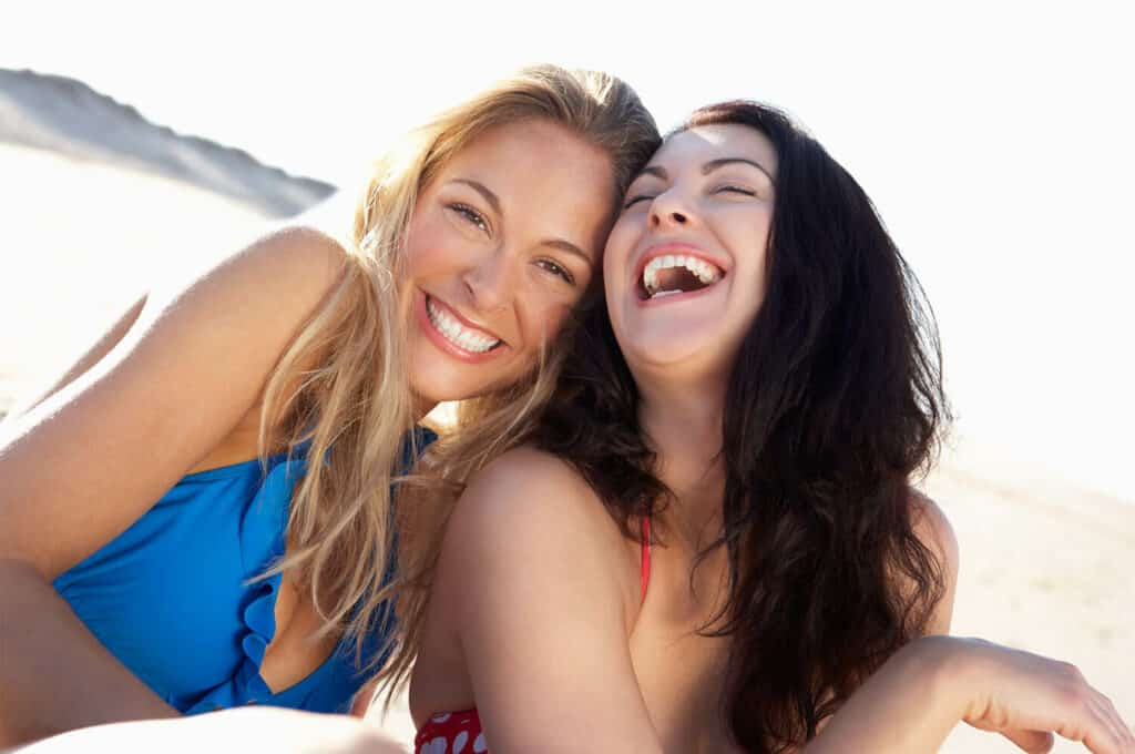 two young white women leaning with heads together while smiling and laughing