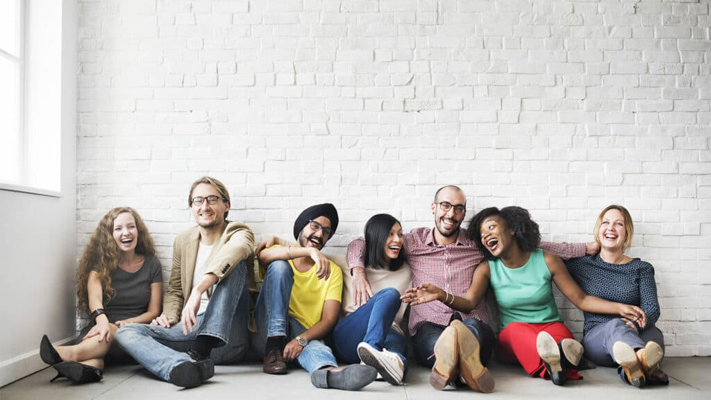 group of mixed race friends sitting together on the floor smiling